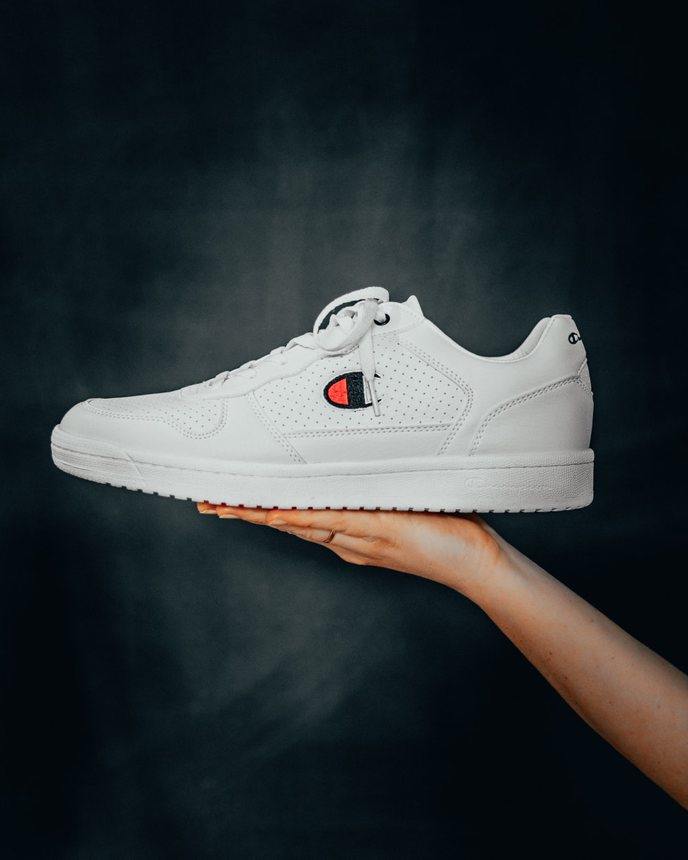 unpaired white Champion low-top sneaker
