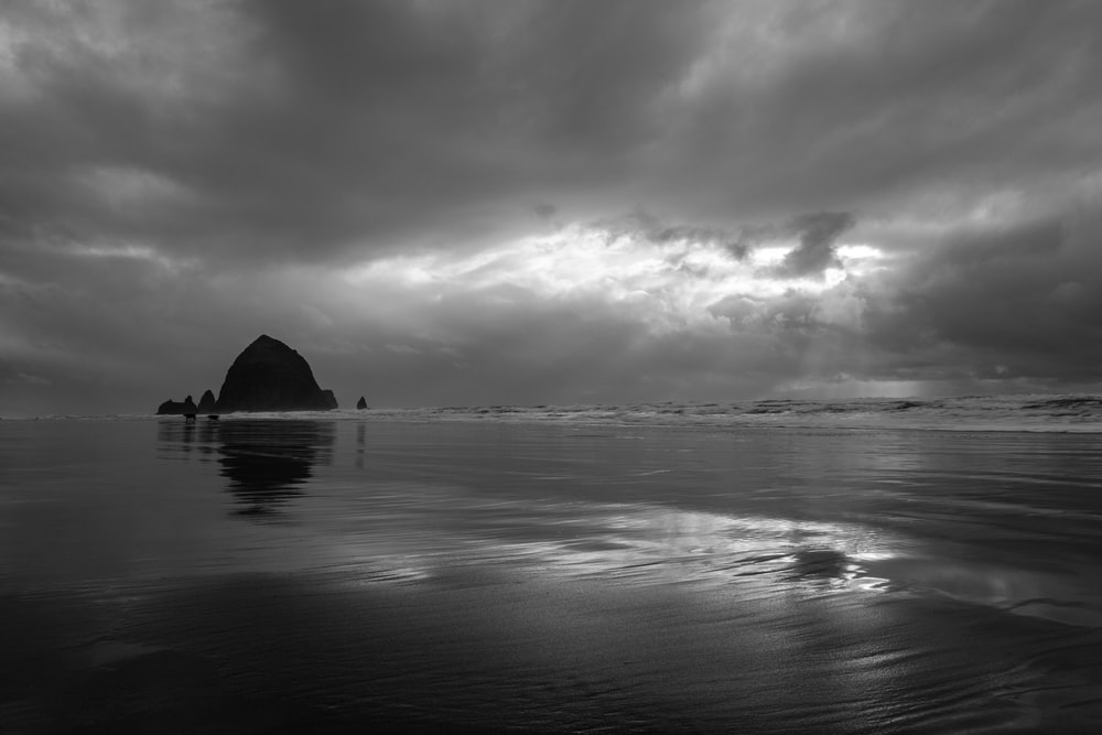 grayscale photography of island under clouds