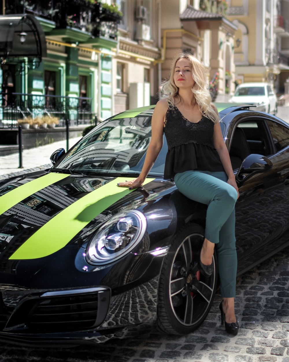 woman leaning on black coupe