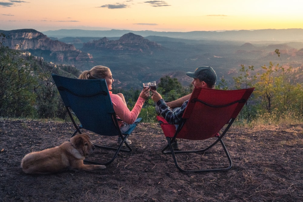 two person sitting on camping chairs while watching mountain