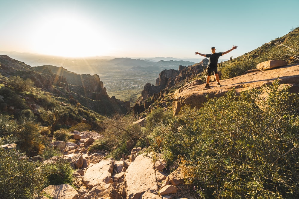 man standing on rocky mountain during day