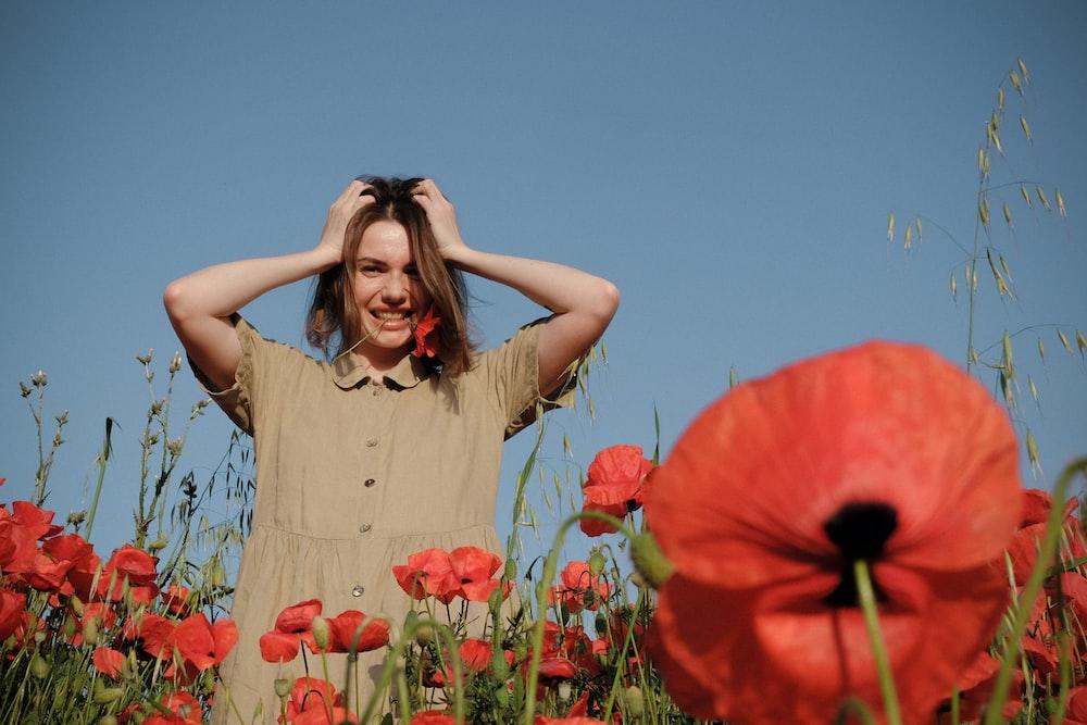 woman in brown dress standing on red flower field