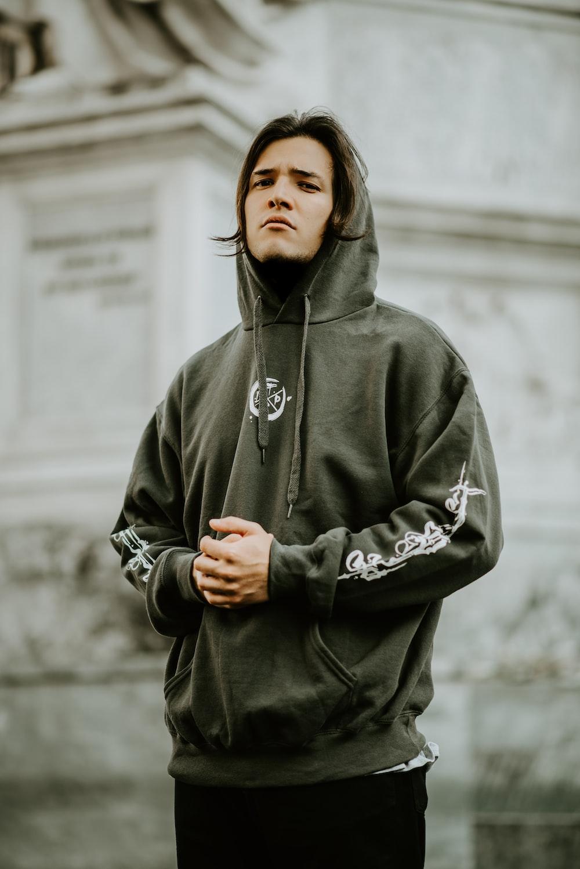 man standing wearing hoodie in front of building