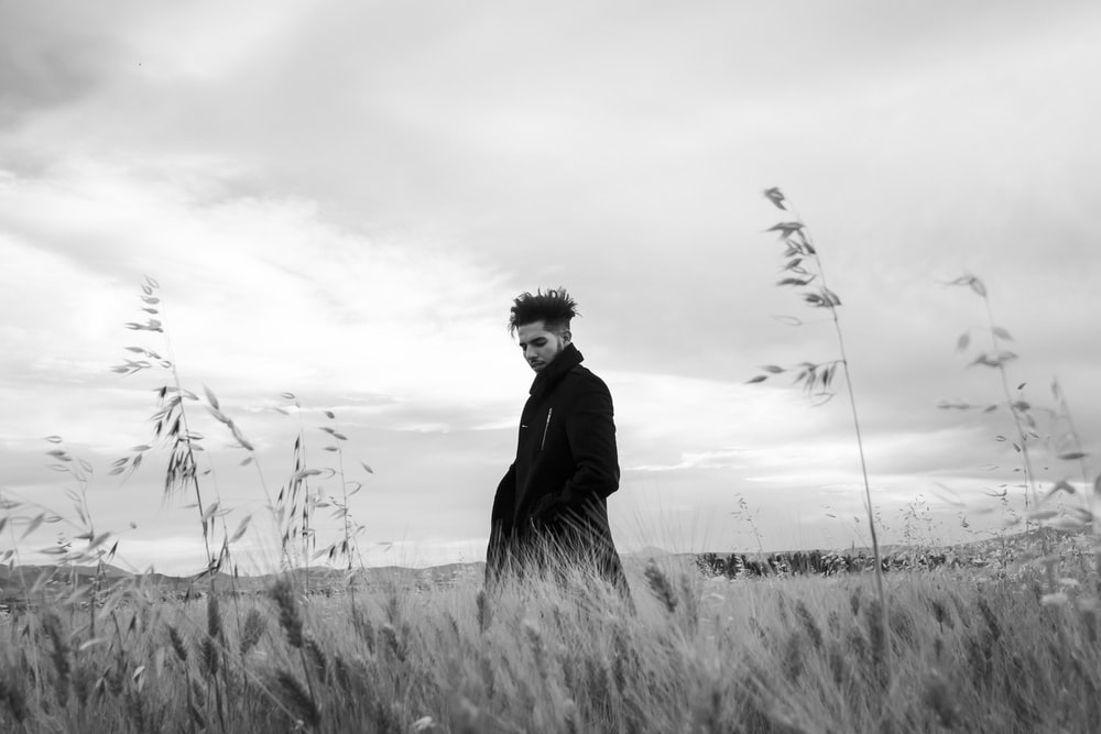 grayscale photography of man standing on grass field