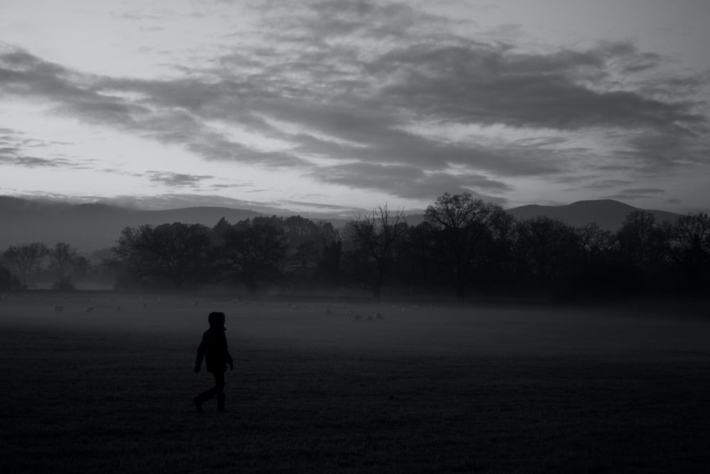 grayscale photo of person walking in the middle of forest