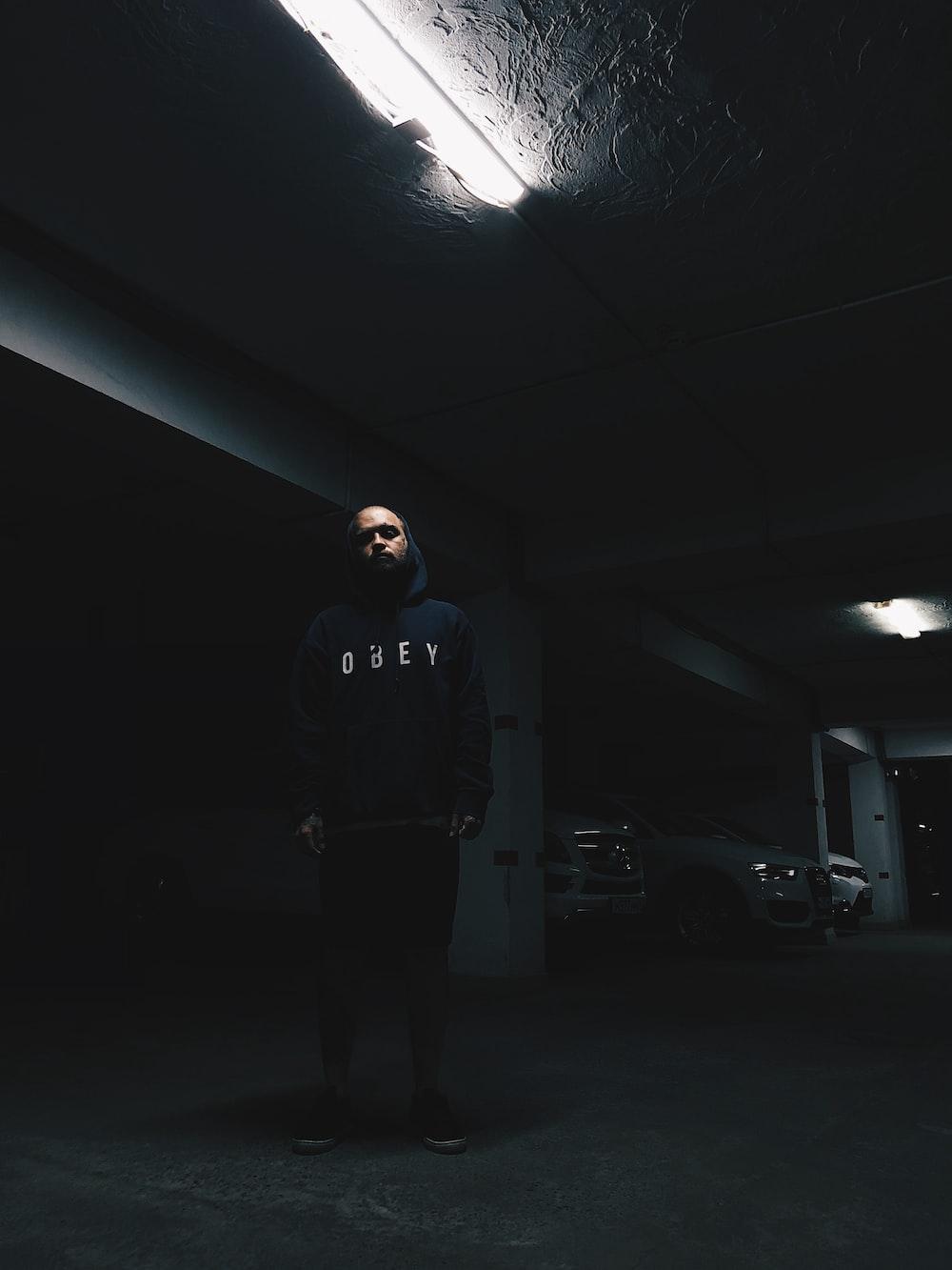 man standing inside building parking lot