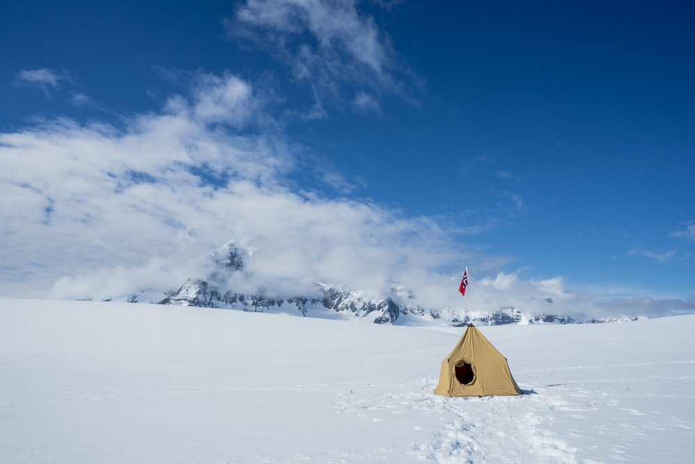 brown tent at the snow during daytime