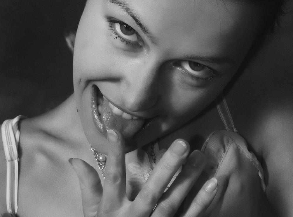 woman putting finger near tongue