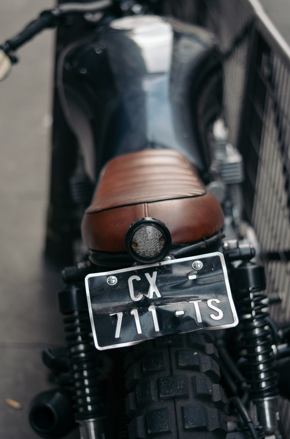black and brown caferacer motorcycle park near metal railings