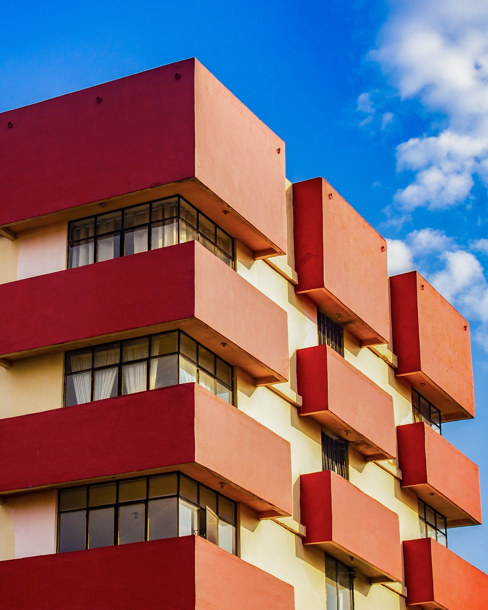red and yellow concrete multi-storey building under blue sky