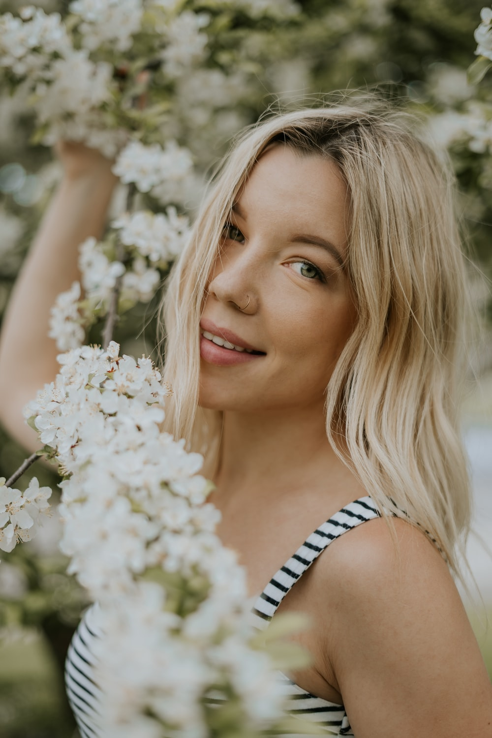 smiling woman standing near white cluster flowers during daytime