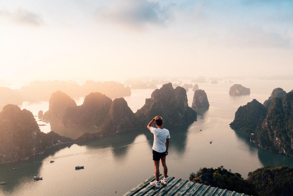 man standing on hill overlooking islands
