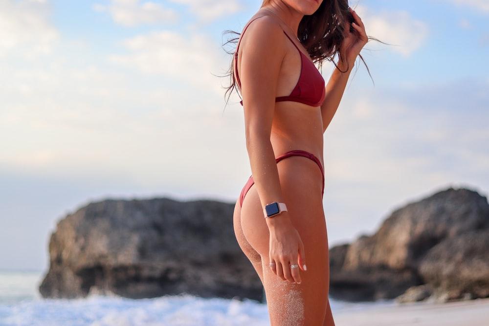 woman in red bikini standing on seashore during daytime