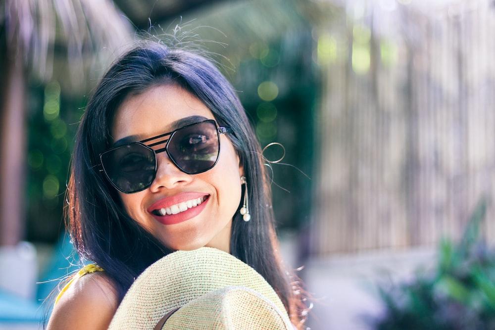 smiling woman wearing black sunglasses taking selfie