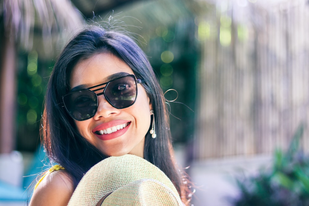 smiling woman wearing black sunglasses taking selfie