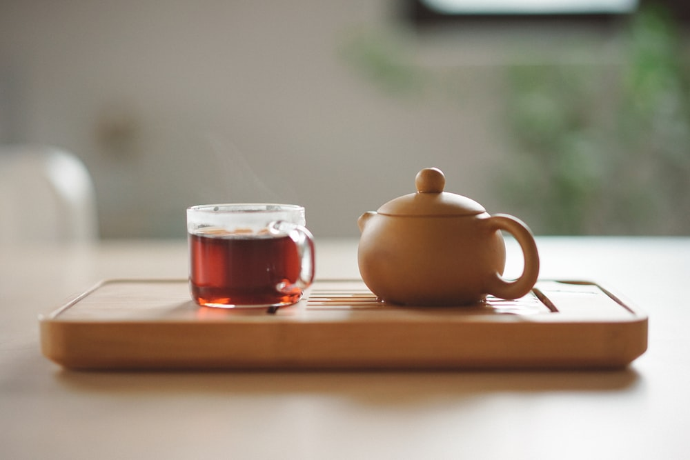 clear glass cup with tea near brown ceramic teapot