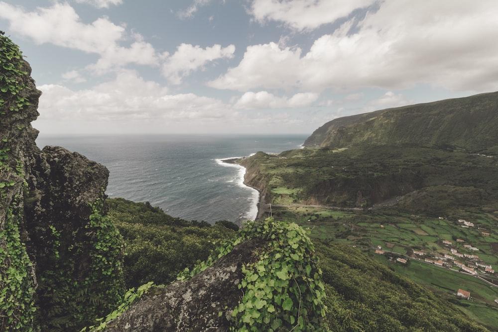 village in between cliff near ocean