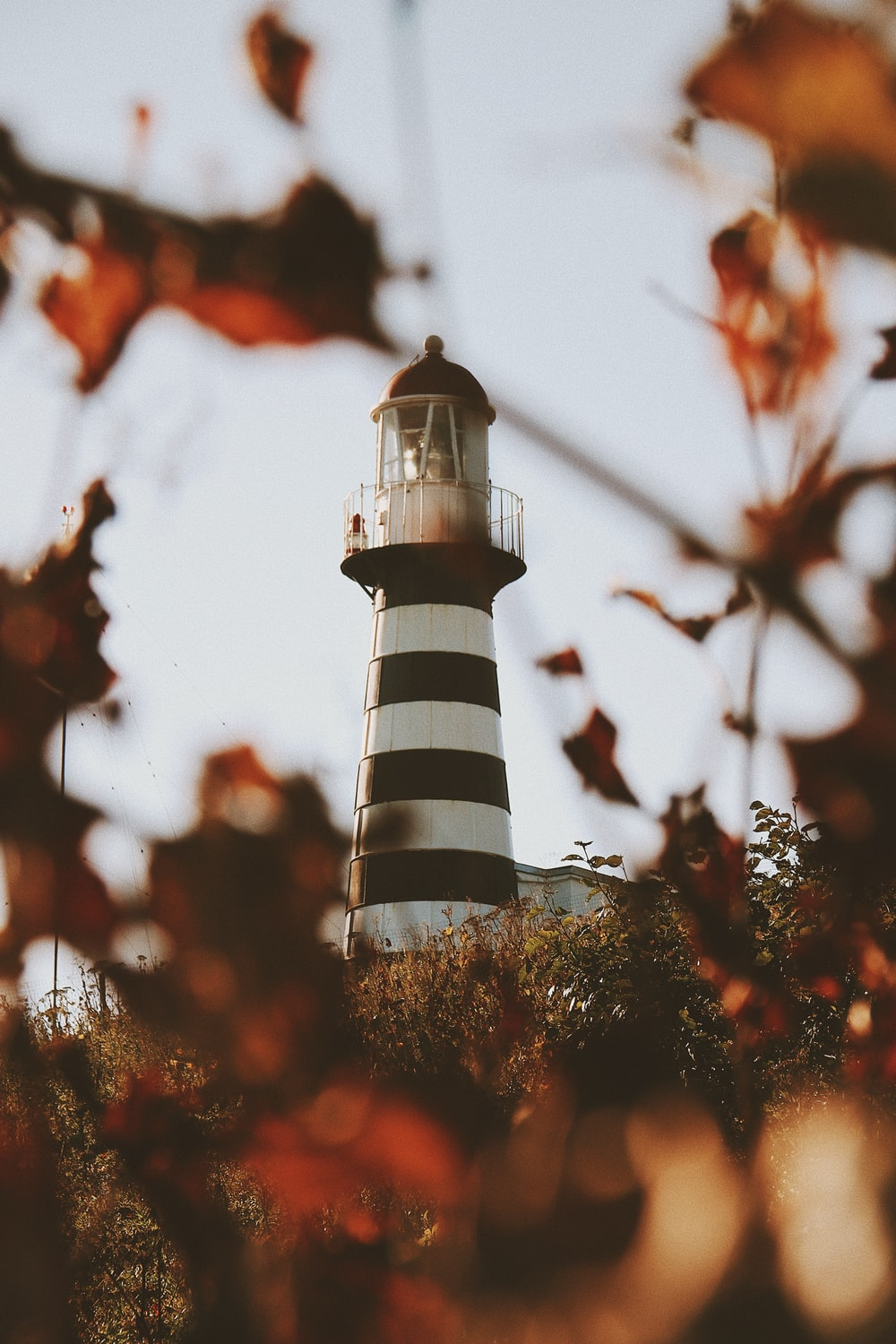 low angle photo of black and white stripe lighthouse tower during daytime