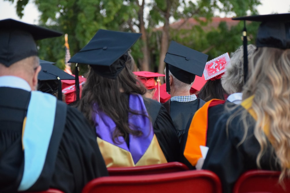 graduates sitting on chair during daytime