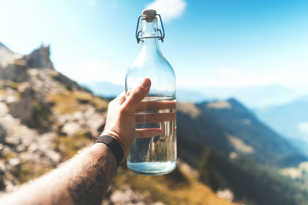 person holding empty clear glass bottle