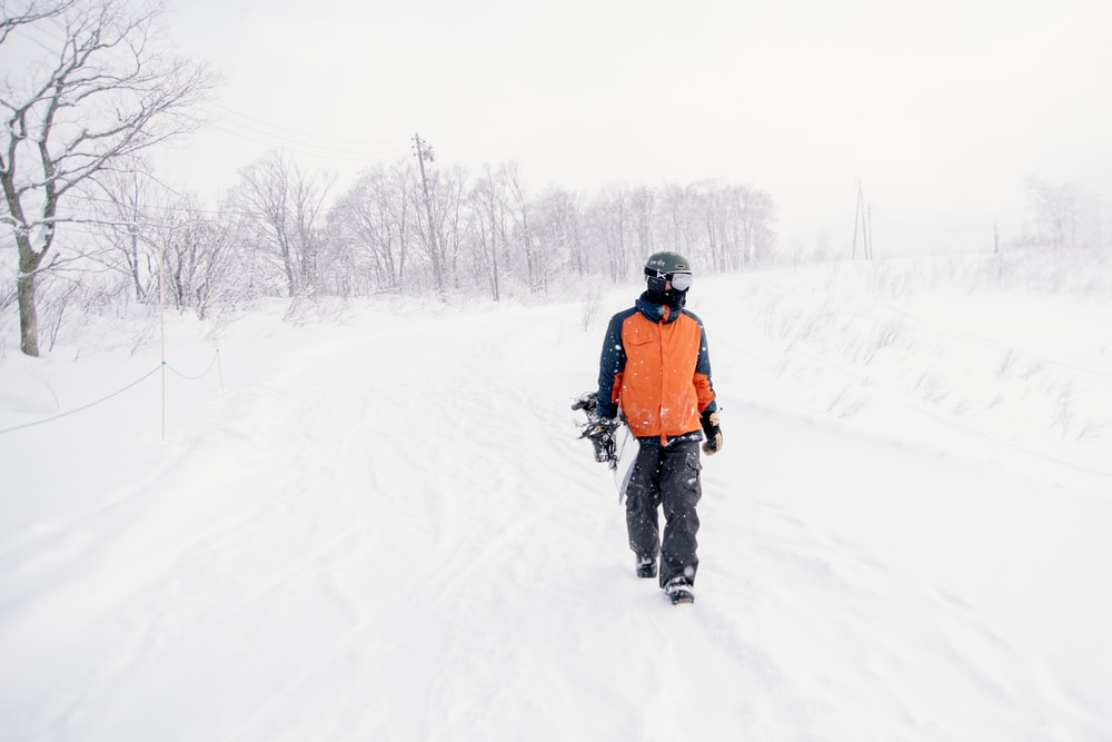 person in orange and black outfit holding snowboard