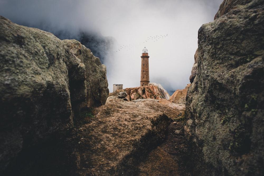 lighthouse on cliff near rock mountain