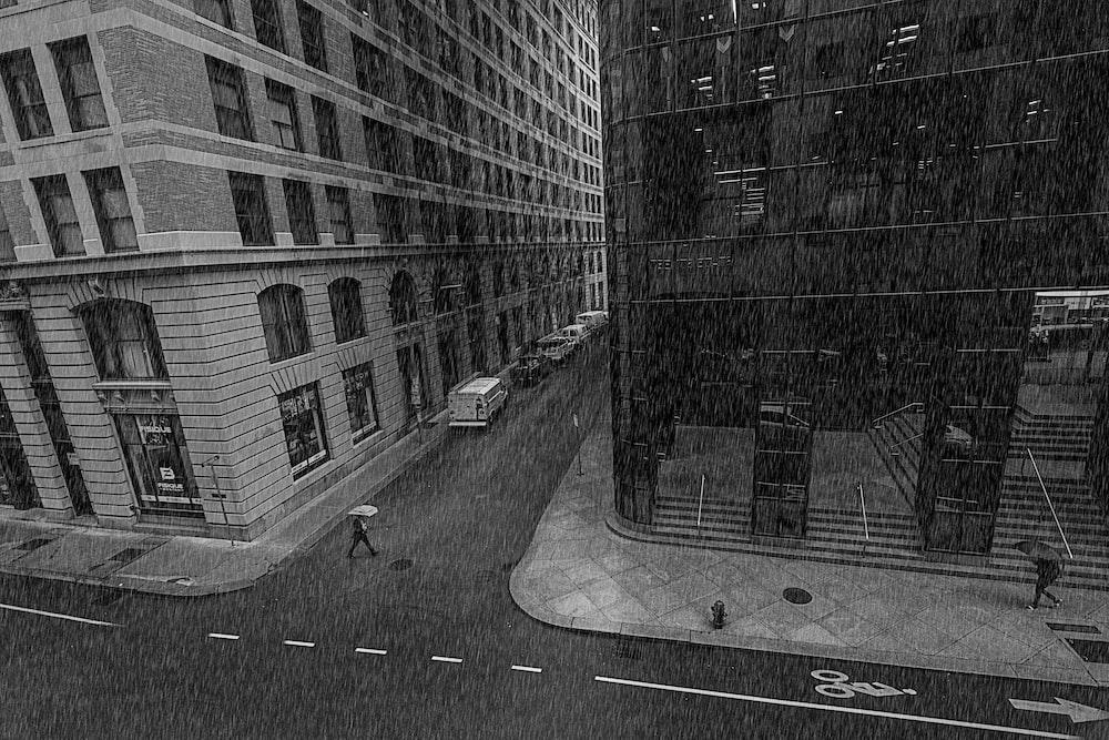 grayscale photo of street between buildings