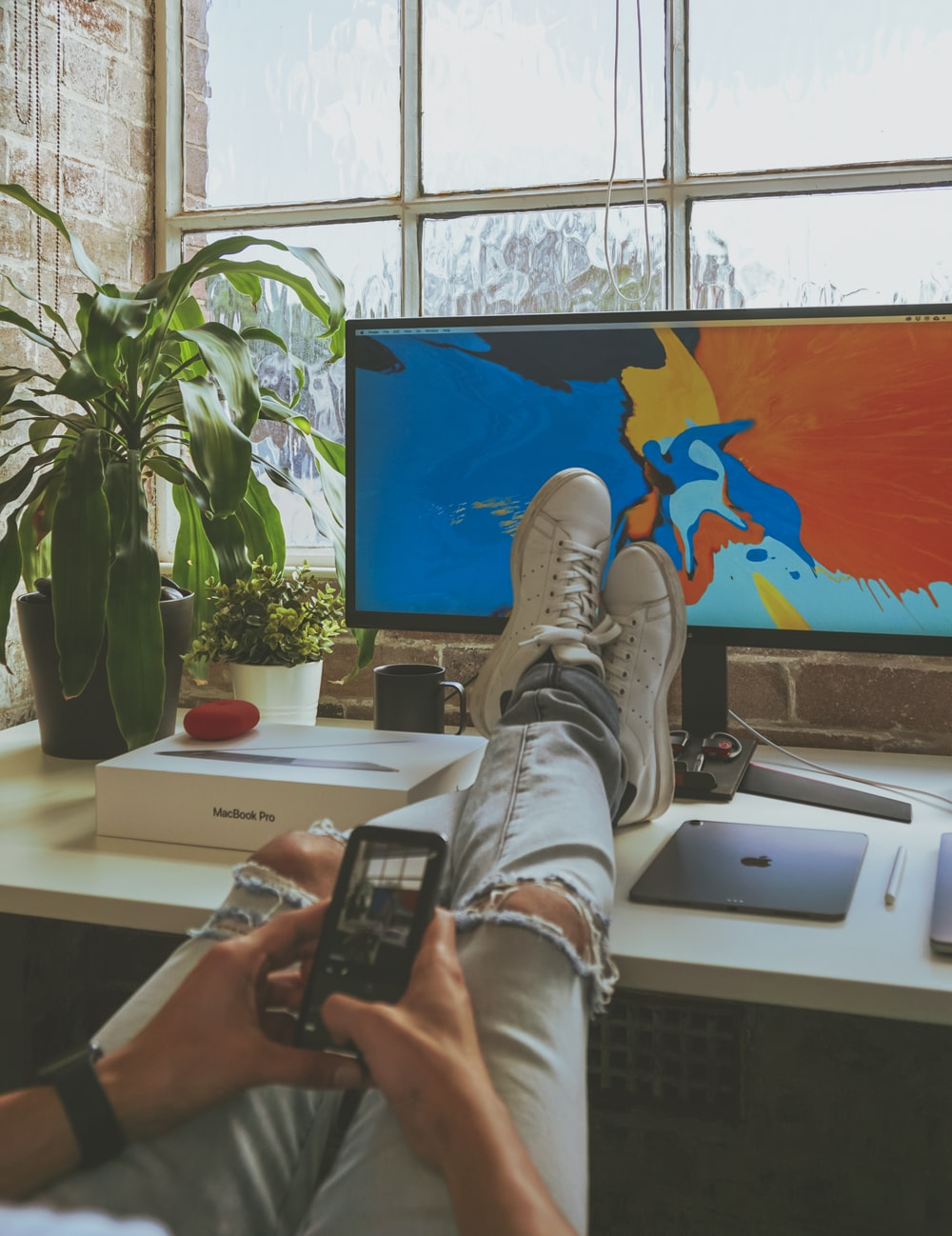 person using smartphone while resting both feet on computer desk