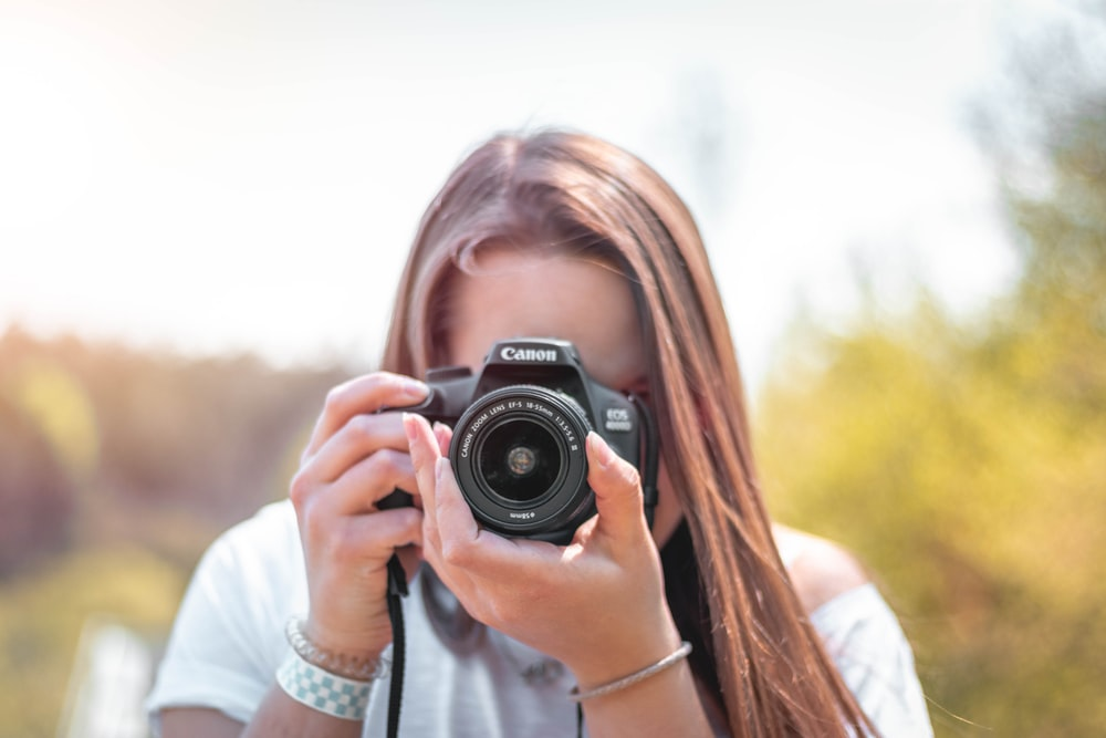 women holding a camera close-up photography