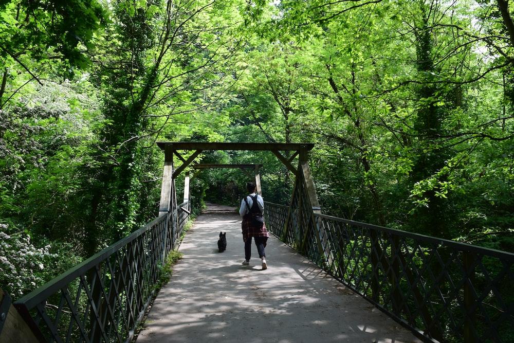 man walking in bridge during daytime