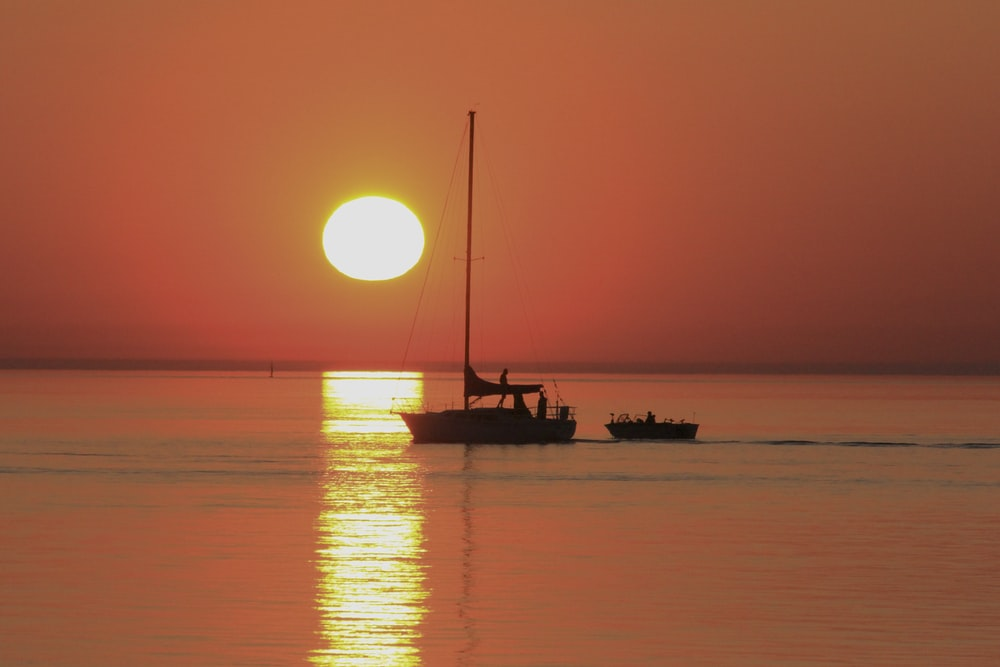 silhouette photography of boat floating in the sea during golden hour