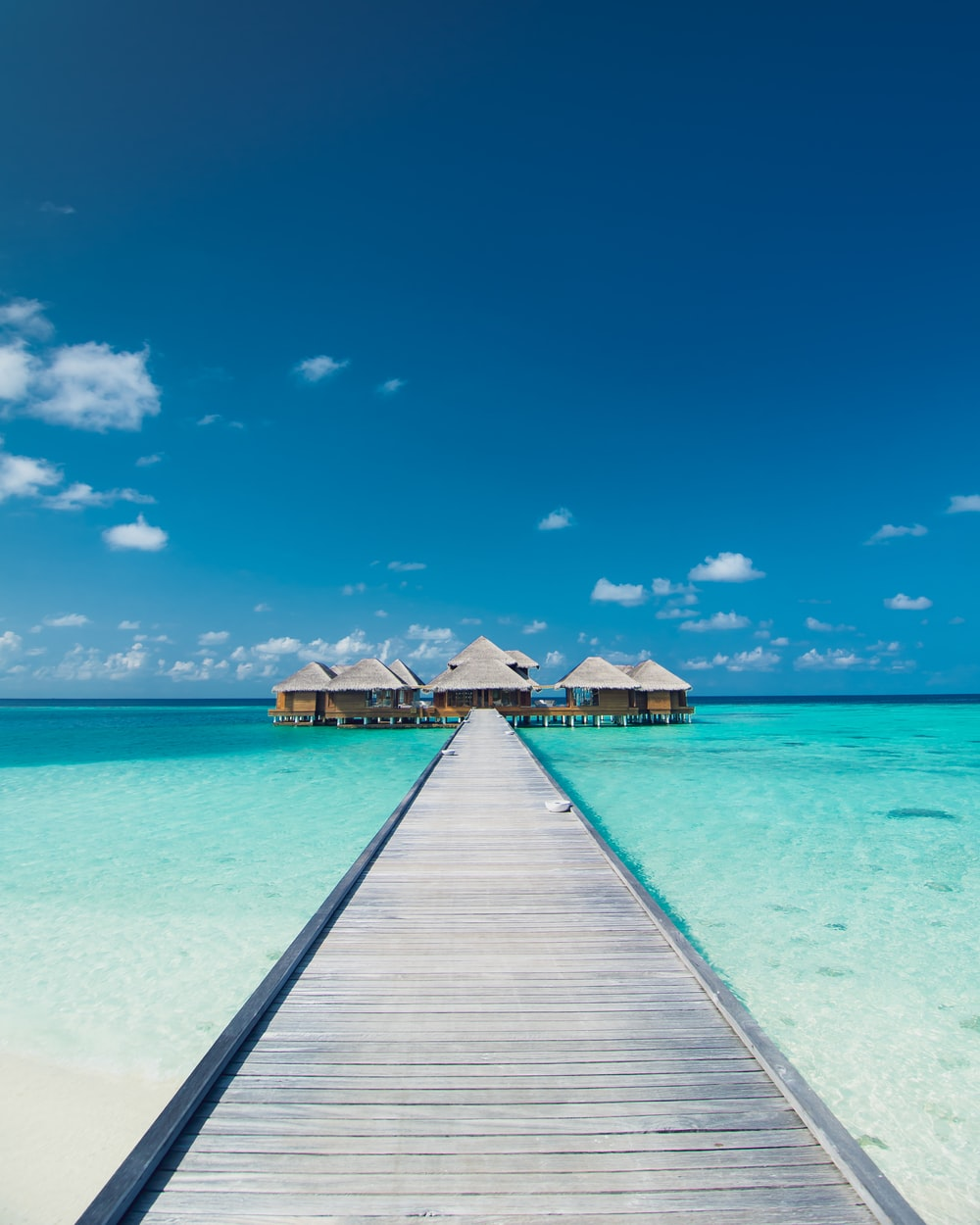 empty wooden dock on clear blue sea under clear blue sky during daytime