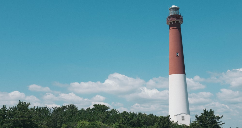 red and white concrete lighthouse under blue sky