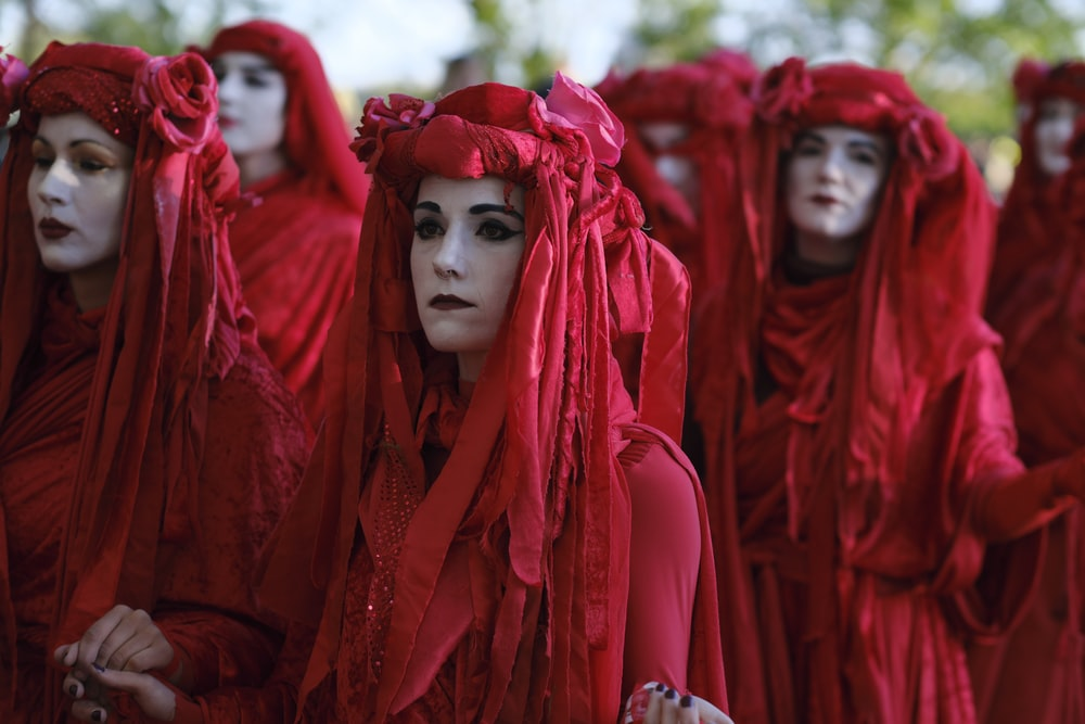 people wearing red dresses and headdresses