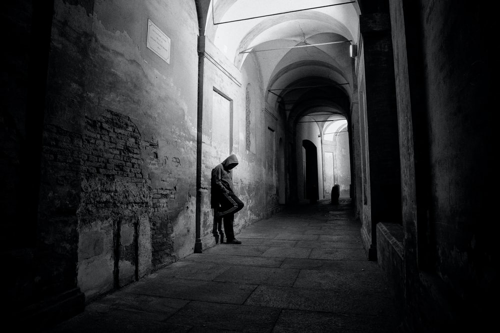grayscale photo of man in hoodie leaning on alley wall