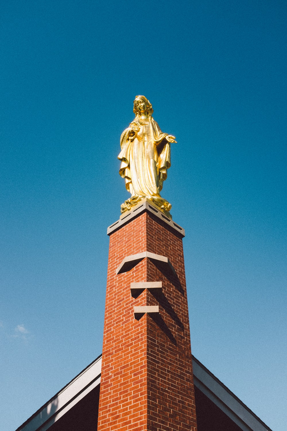 low angle photo of statue on tower