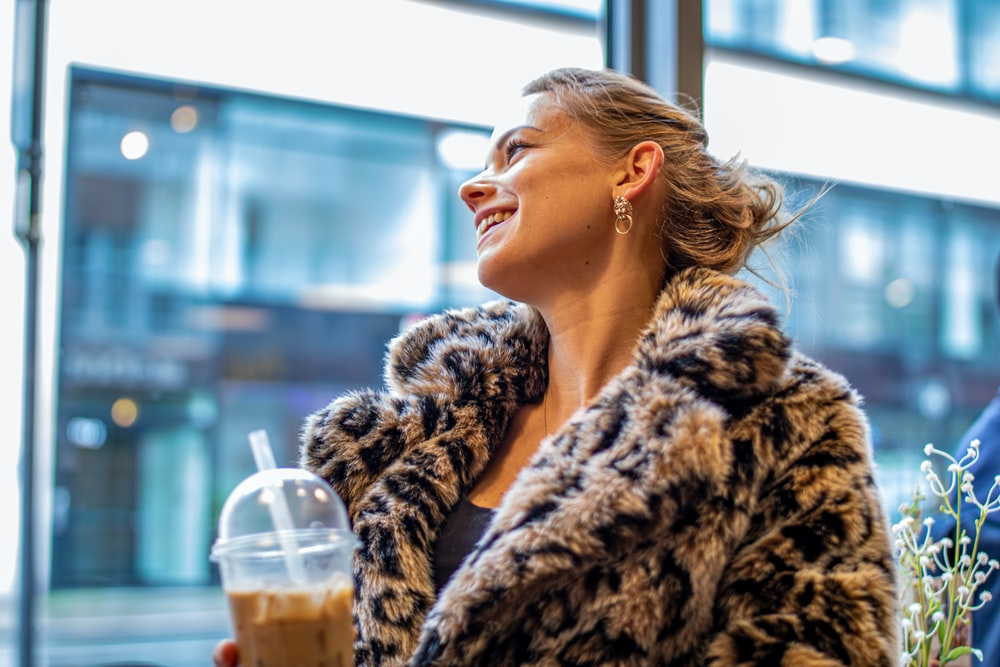 woman in brown coat holding cup