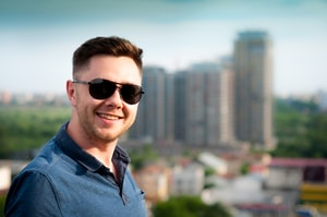 Man with glasses and a blue polo shirt standing in front of city skyline smiling