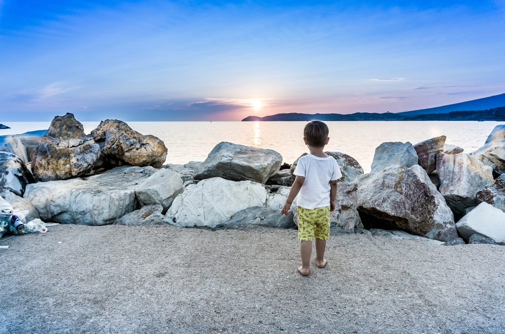 boy standing by a seawall