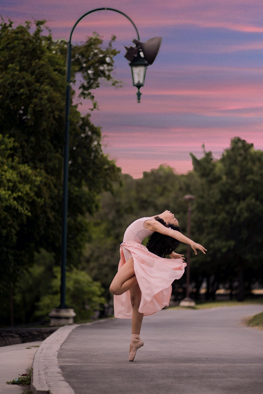 ballet dancer on road beside street lamp