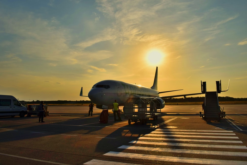 white airplane parked during daytime