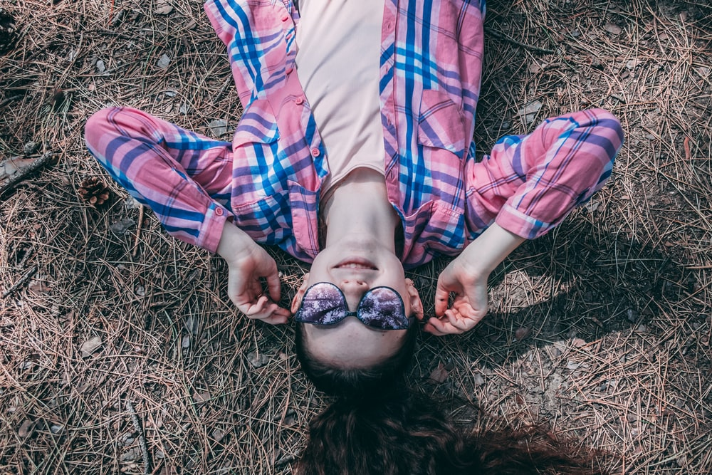 woman lying on ground with wilted grass
