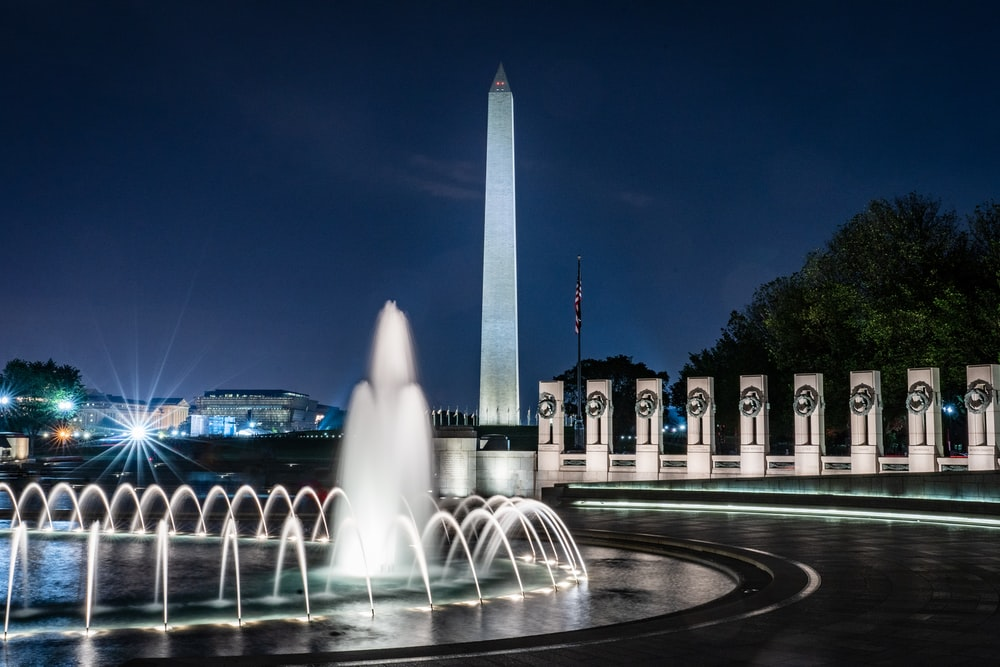 lighted tower building near water fountain in timelapse photo