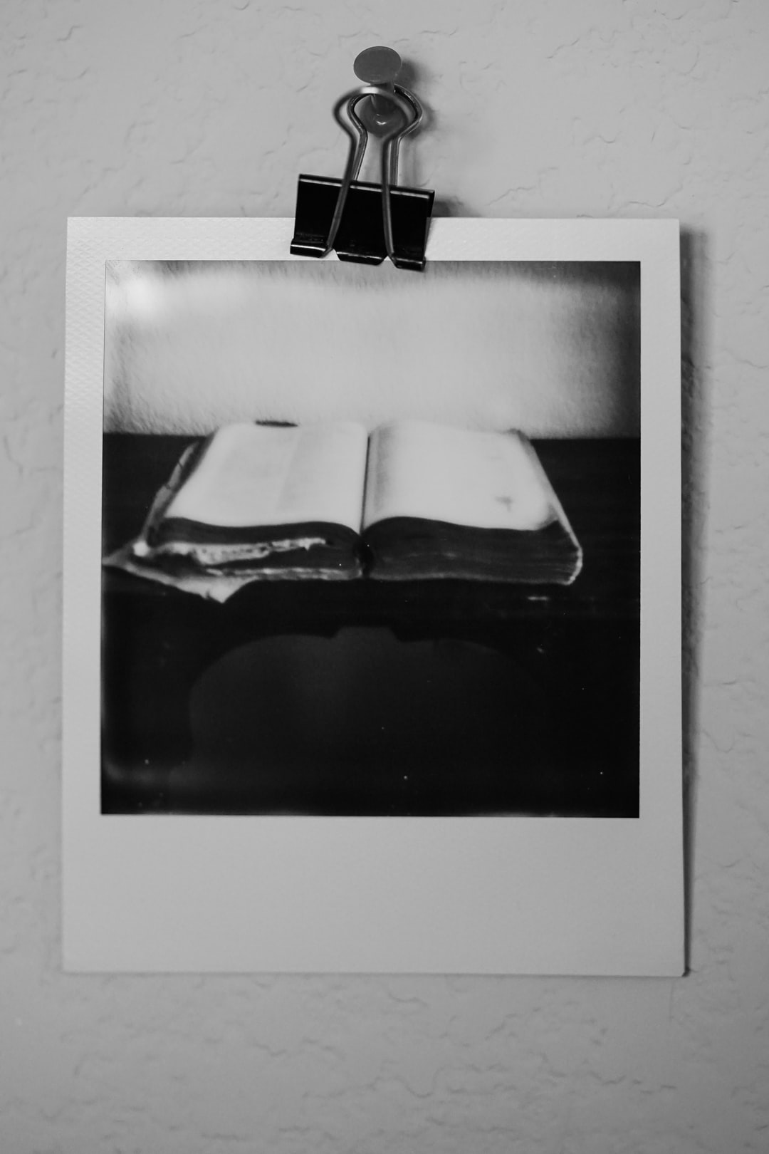 Black and white Polaroid instant film photograph of an open book on a table.