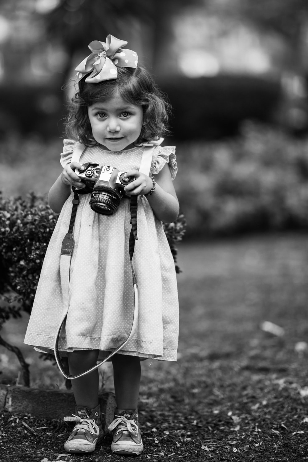 girl holding DSLR camera in grayscale photo