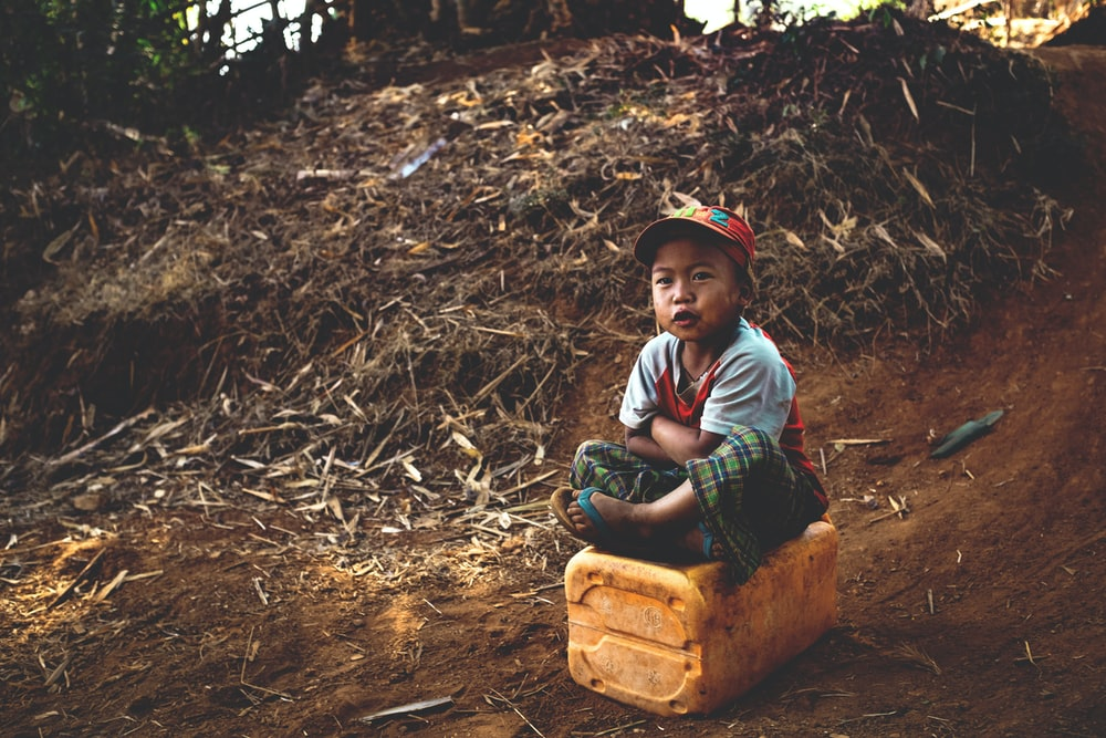 boy sitting on yellow container