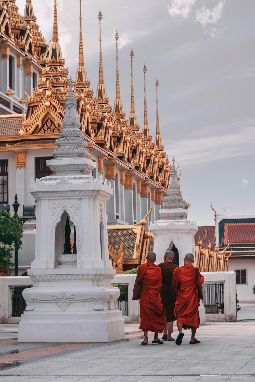 three monks walking beside temple