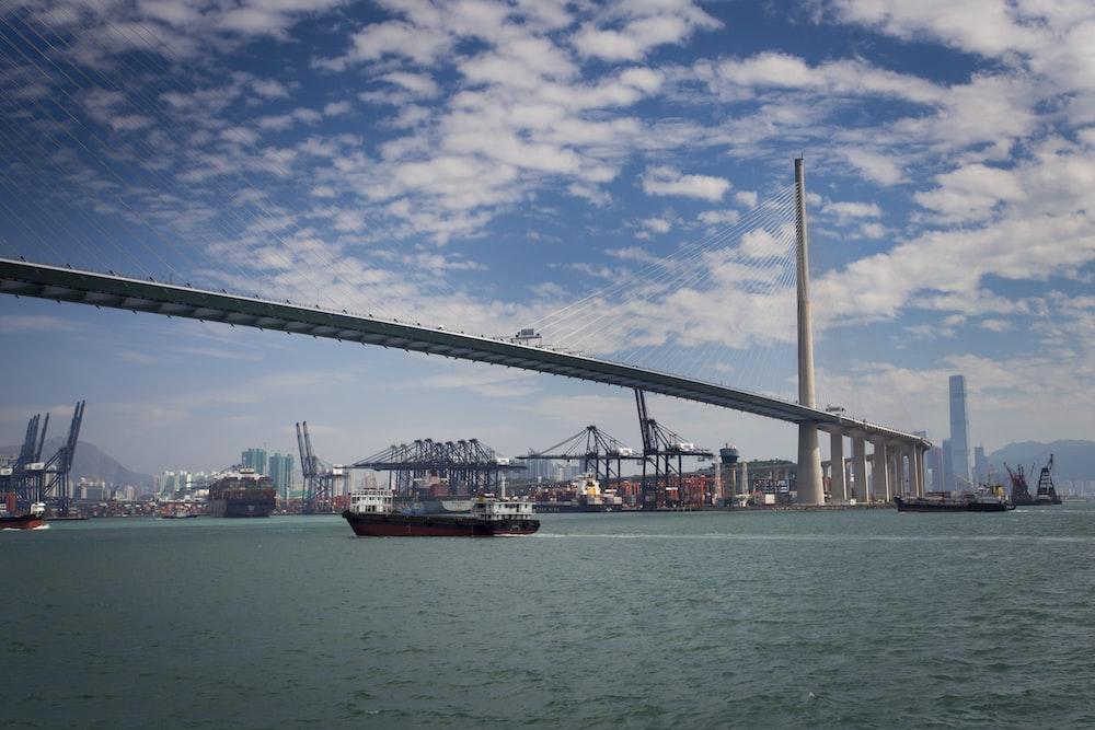 ship passing by under an iron bridge