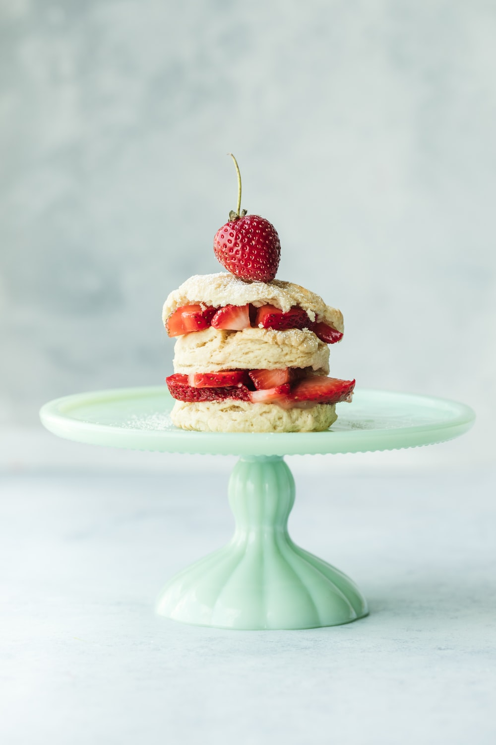 cake with strawberries on teal ceramic cake stand