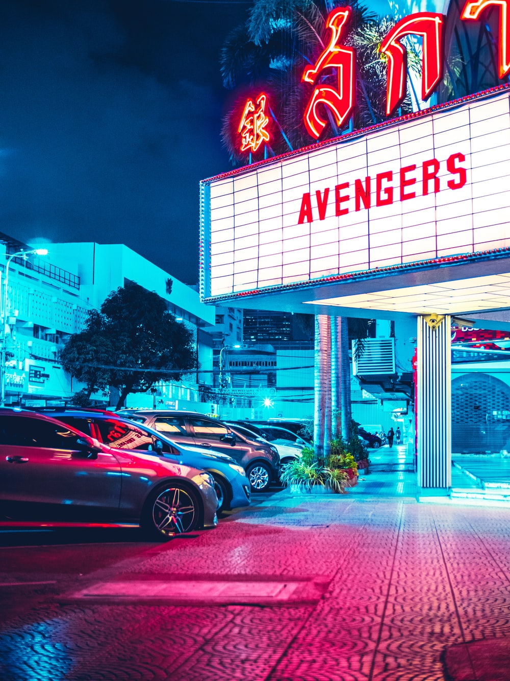 vehicles parked beside Avengers signage